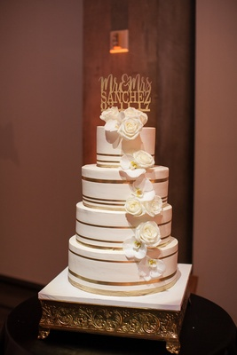 four-tiered wedding cake with gold stripes and sugar flowers of roses and orchids