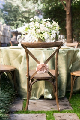 rustic wooden chair with pink flower rosette and green table linens with lush floral arrangement