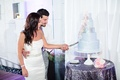 Bride in a strapless Vera Wang dress, beaded sash and groom in white shirt, grey pants, cut cake