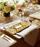 Gold velvet name card with monogram napkin at reception