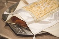 Challah draped with a white cover with gold embroidery on silver tray for a Jewish wedding reception