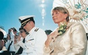 Military officer and mother of the groom shade themselves with umbrella