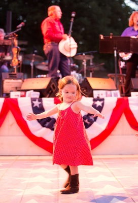 Little girl in red dress on dance floor at bbq