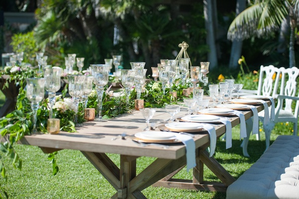 Garden wedding reception with rustic wood table with greenery, white flowers, glass candleholders