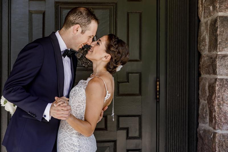 bride in custom hayley paige wedding dress and back necklace, groom in navy tuxedo