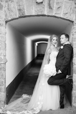 Black and white photo of bride and groom in hallway archway bride in strapless gown groom in tuxedo
