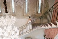 Bride in illusion wedding dress walking up stairs of chateau venue in the South of France