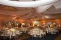 White fabric draped from ceiling over wedding tables