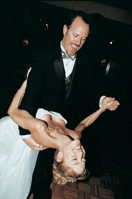 Smiling newlyweds dancing at reception