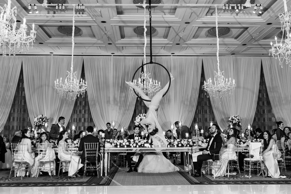 black and white photo of aerialist over head table amongst chandeliers and reception decorations