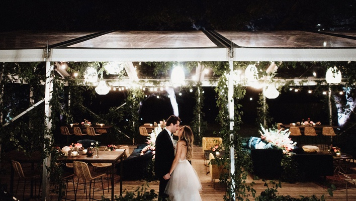 bride and groom kiss in front of reception tent with lounge furniture string lights boho design