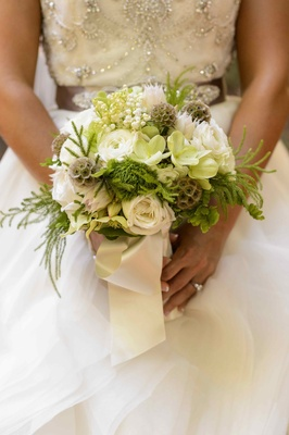 Bride holding lily of the valley and scabiosa pods
