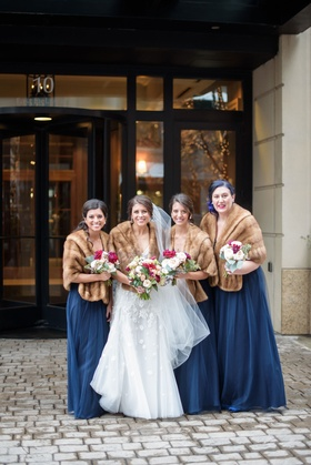 Bride in wedding dress bridesmaids in blue bridesmaid dresses brown fur stoles grandmother bouquets