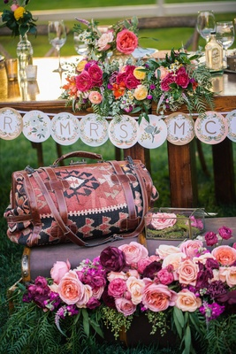Outdoor wedding reception with a closed antique suitcase filled with a variety of pink, peach roses