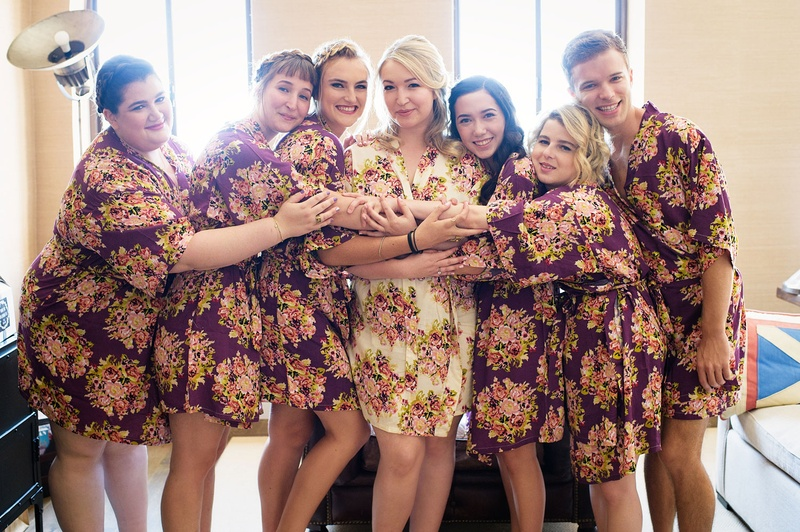 Bride in white floral robe and bridesmaids in purple flower robes in bridal suite hugging