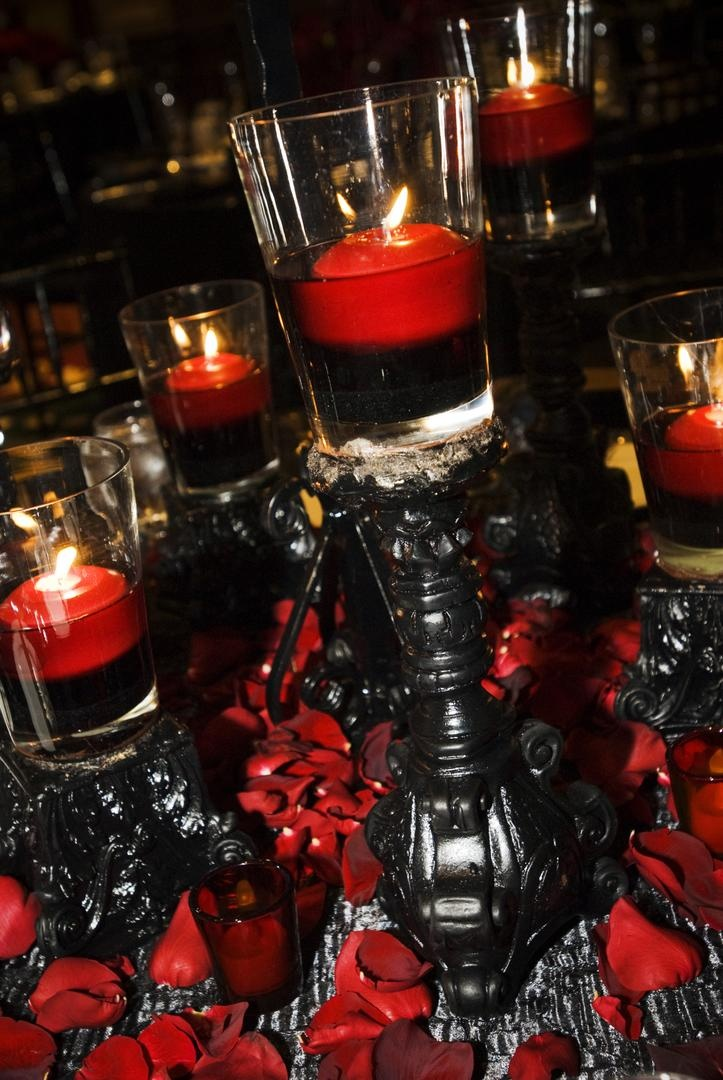 Wedding reception table with black candelabra with red candles floating in red water