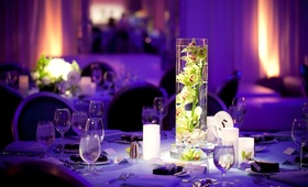 Lime green flowers in cylinder vase at purple wedding