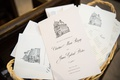 wedding ceremony programs in wicker basket grey lettering drawing of catholic church on top