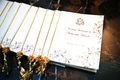 Wedding program with a ganesh illustration and golden tassel