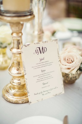 Wedding menu on reception table with three initial wedding monogram and gold candle riser mercury