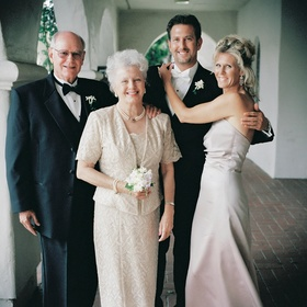Fancy guests in tuxedos and formal gown and mother of the bride dress