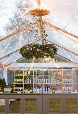 tent wedding, string lights, greenery chandelier, bar