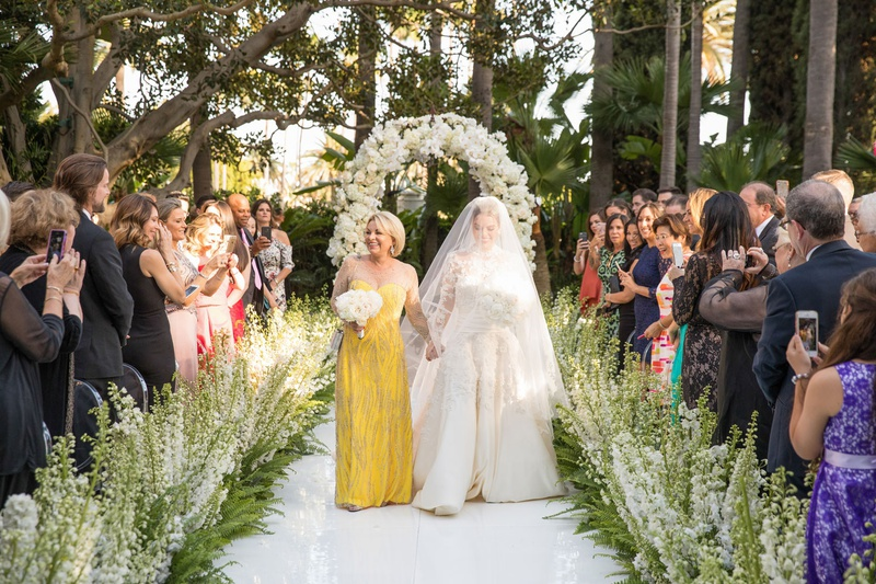 Bride in long sleeve wedding dress and veil with mother of bride in illusion neckline yellow dress
