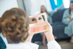 bride looking in mirror to see makeup