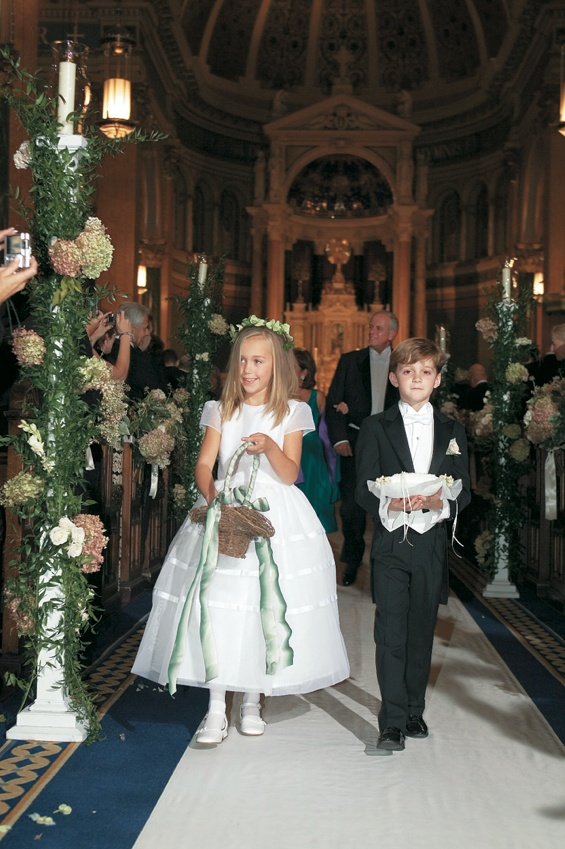 Cute boy and girl walking down church aisle