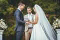 bride in stella york wedding dress, groom in navy suit, officiant in khaki suit