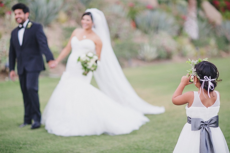 Flower girl taking picture of the bride and groom outdoors