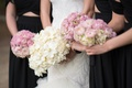bride with bouquet of ivory flowers, bridesmaids with pink bouquets