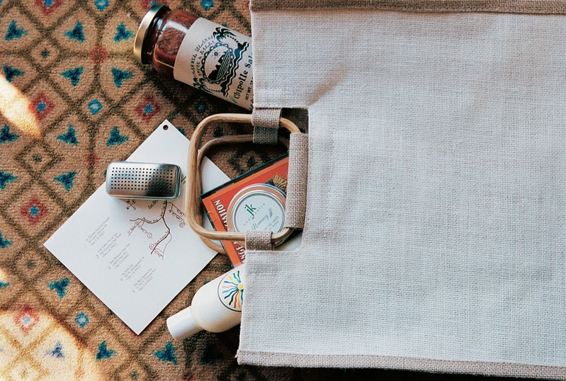 linen bag filled with map, lotion to welcome guests