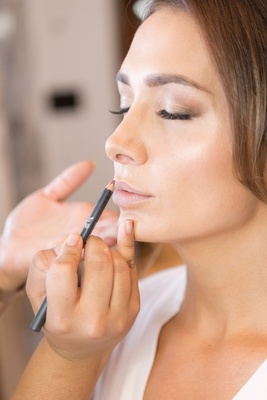 Bride with brown hair getting lip liner put on in bridal suite white robe makeup look natural