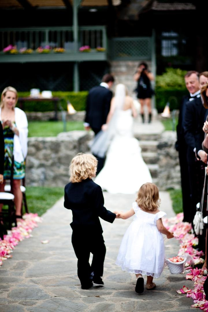 Flower girl and ring bearer hold hands and walk up aisle