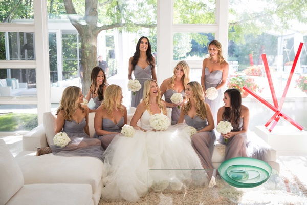 Bride in Vera Wang wedding dress with bridesmaids in light grey dresses on white couch at home