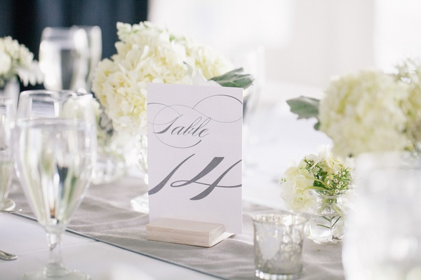 Light wood stand holding white table number