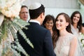 Bride smiles at groom in yarmulke at Jewish wedding ceremony chuppah Sabrina Dahan dress