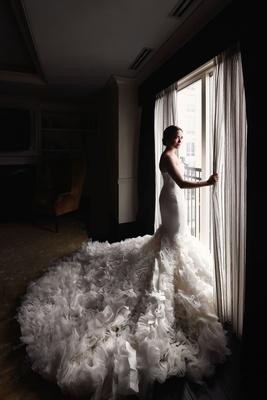 wedding portrait bride looking out window strapless wedding dress mermaid gown textured ruffle skirt