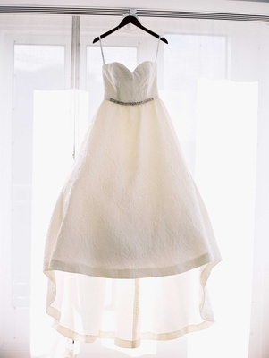Wedding dress hanging up in window strapless sweetheart neckline ballgown with train