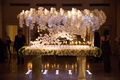 Escort card table with lucite and orchid details flower garland around edge of table top