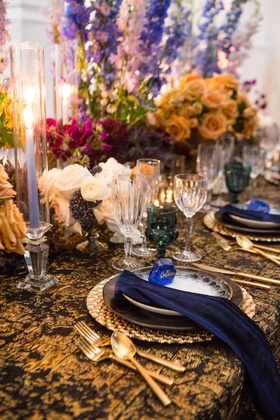 wedding styled shoot, periwinkle tapered candles, bright flowers teal glassware, black & gold linens
