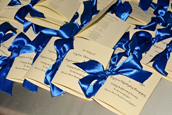 White and ivory ceremony program tied with royal blue satin ribbon