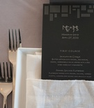 Art Deco-inspired menus in white linen napkin