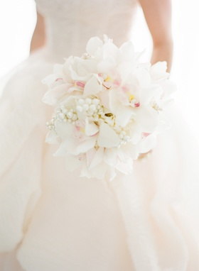 Bride holding orchids, pearls, and peonies