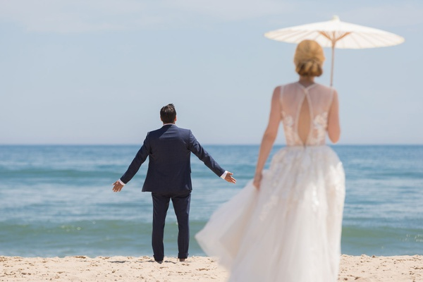 wedding portrait groom with arms out beach in montauk new york bride in dress parasol