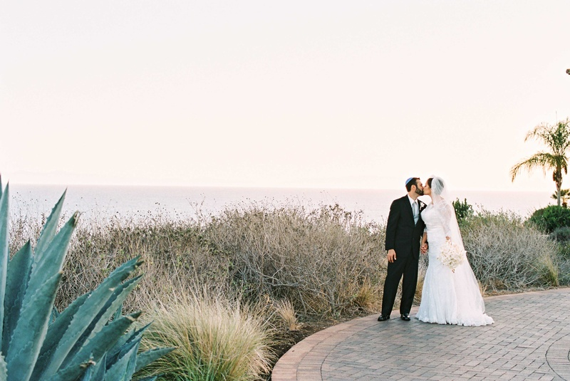 Bride in Alfred Angelo wedding dress groom in tuxedo at Terranea wedding venue in California