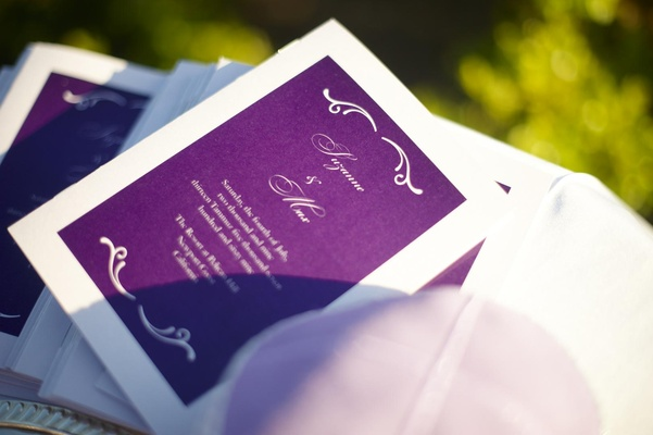 Wedding program with white script and purple background