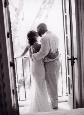Black and white photo of couple kissing in doorway