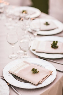 Wedding guest place setting with silver charger plate, tan napkin, menu, and green succulent detail